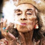 """Женщина лет 80 в платье """"под Зебру"""", с крупными серьгами в ушах и ярким алым маникюром разговаривает по телефону у входа в """"буланжери"""":"""